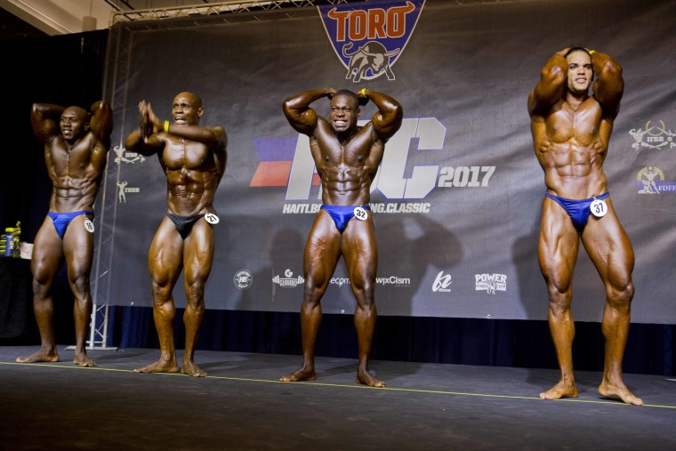 In this July 23, 2017 photo, Haitian bodybuilder Spely Laventure, center, performs alongside Dominican Jose Solano, right, and other Haitian athletes during a bodybuilding competition between Haiti and Dominican Republic in Port-au-Prince, Haiti. More than two dozen men and one woman competed in Sunday's Haiti Bodybuilding Classic. Laventure won the semi-heavy weight category, as well as first for overall show, and said he hopes it will lead to sponsors and more exposure. Solano placed second in the super-heavy weight category. (AP Photo/Dieu Nalio Chery)
