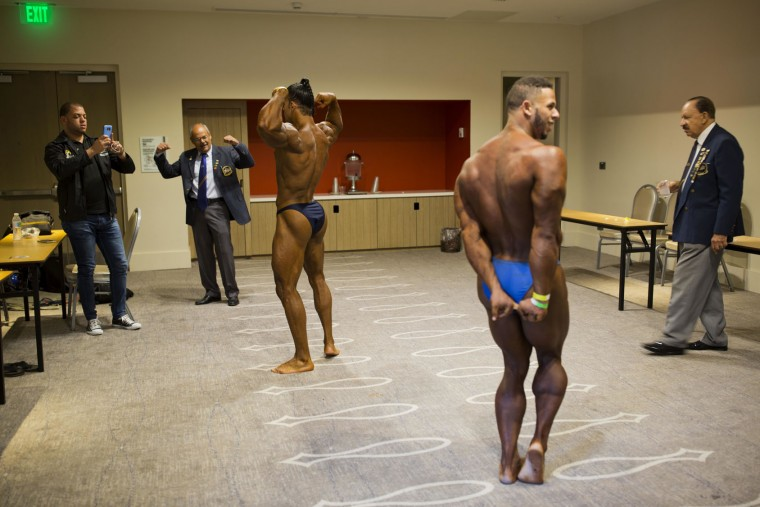 In this July 23, 2017 photo, Dominican Republic bodybuilders Jose Solano, left, and Emmanuel Hidalgo pose for photos and prepare for a competition between Haiti and Dominican Republic in Port-au-Prince, Haiti. Sunday's event was organized by the Dominican bodybuilding federation and a local Haitian bodybuilding group to generate support for the sport and make it more accessible, especially in Haiti where a handful of bodybuilders struggle to become professionals in a country where people make less than $2 a day. (AP Photo/Dieu Nalio Chery)