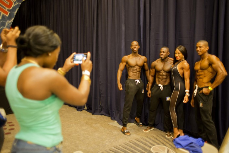 "In this July 23, 2017 photo, Haitian bodybuilder Spely Laventure, third from right, takes pictures with a fan and fellow Haitian bodybuilders before a competition between Haiti and Dominican Republic in Port-au-Prince, Haiti. ""I spent all my savings on my body. I don't regret that,"" said the a 30-year-old. (AP Photo/Dieu Nalio Chery)"