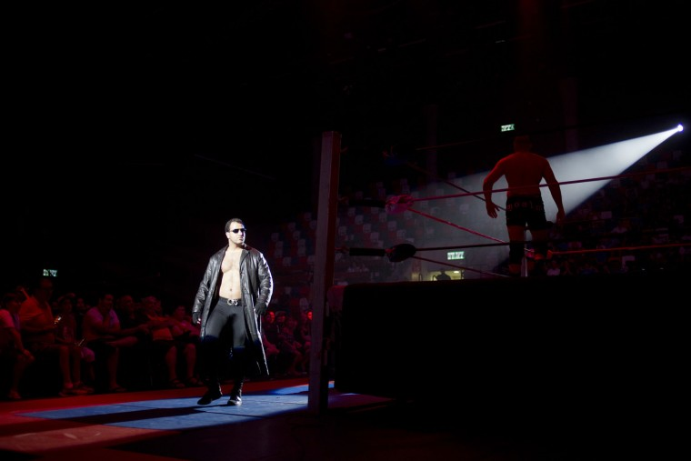 Wrestler The Boss, left, walks to the ring while Wrestler Joey Tylec stands during The Rage Wrestling Mega Show in Tel Aviv, Israel, Sunday, July 9, 2017. The Israeli Wrestling League hosted a wrestling show in Tel Aviv with Kevin Von Erich and some of the WWE greatest of all time. (AP Photo/Ariel Schalit)