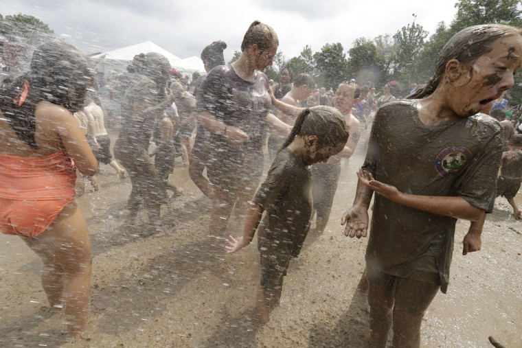 Kids wash off after playing in the mud during Mud Day at the Nankin Mills Park, Tuesday, July 11, 2017 in Westland, Mich. The annual day sponsored by the Wayne County Parks takes place in a 75' x 150' giant mud pit that gives children the opportunity to get down and dirty at one of the messiest playgrounds Southeast Michigan has ever seen. (AP Photo/Carlos Osorio)