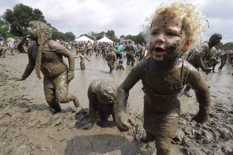 Kids play in the mud during Mud Day at the Nankin Mills Park, Tuesday, July 11, 2017 in Westland, Mich. The annual day sponsored by the Wayne County Parks takes place in a 75' x 150' giant mud pit that gives children the opportunity to get down and dirty at one of the messiest playgrounds Southeast Michigan has ever seen. (AP Photo/Carlos Osorio)