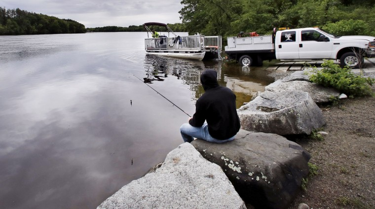 "In this Wednesday June 7, 2017 photo, Kevin Garcia fishes along the banks of the Merrimack River as a ""Clean River Project"" recovery boat is offloaded in Chelmsford, Mass. Syringes left by drug users amid the heroin crisis are turning up everywhere. They hide in weeds along hiking trails and in playground grass, get washed into rivers and onto beaches, and lie scattered about in baseball dugouts and on sidewalks and streets. There are reports of children finding them and getting poked. (AP Photo/Charles Krupa)"