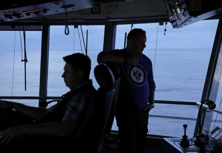 In this Thursday, July 6, 2017 photo, first officer Jukka Vuosalmi, right, and second officer Ilkka Alhoke look out from the bridge during a night shift while piloting the Finnish icebreaker MSV Nordica as it sails the North Pacific Ocean to traverse the Northwest Passage through the Canadian Arctic Archipelago. Most of the 21 regular crew work 12-hour shifts. (AP Photo/David Goldman)