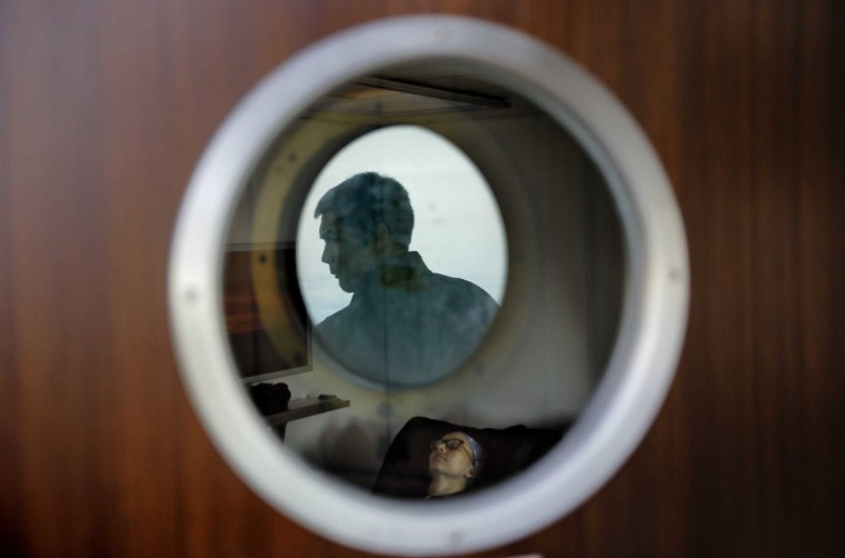 In this Thursday, July 13, 2017 photo, trainee David Kullualik is reflected in a deck door window looking out to sea as researcher Ilona Mettiainen reclines in a massage chair aboard the Finnish icebreaker MSV Nordica as it sails the Bering Sea to traverse the Northwest Passage through the Canadian Arctic Archipelago. (AP Photo/David Goldman)