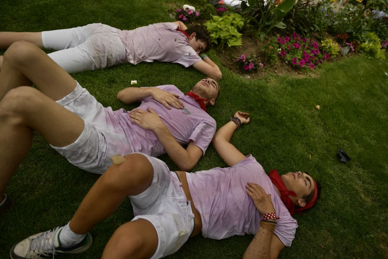 Revellers rest after the launching of the 'Chupinazo' rocket, to celebrate the official opening of the 2017 San Fermin Fiestas in Pamplona, Spain, Thursday July 6, 2017. The first of eight days of the running of the bulls along the streets of the old quarter of Pamplona starts Friday. (AP Photo/Alvaro Barrientos)