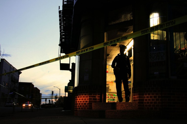 """A police officer looks out of the doorway of Geri's Liquors on Charles Street during an April 2015 shooting investigation."" (Photo and caption courtesy of Maggie Ybarra)"