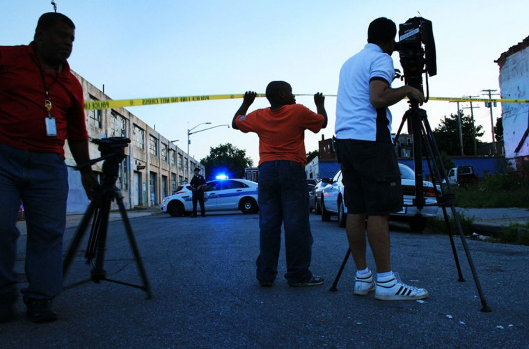 """A child plays with the crime scene tape on Whitelock Street while police investigate a July 2014 shooting."" (Photo and caption courtesy of Maggie Ybarra)"