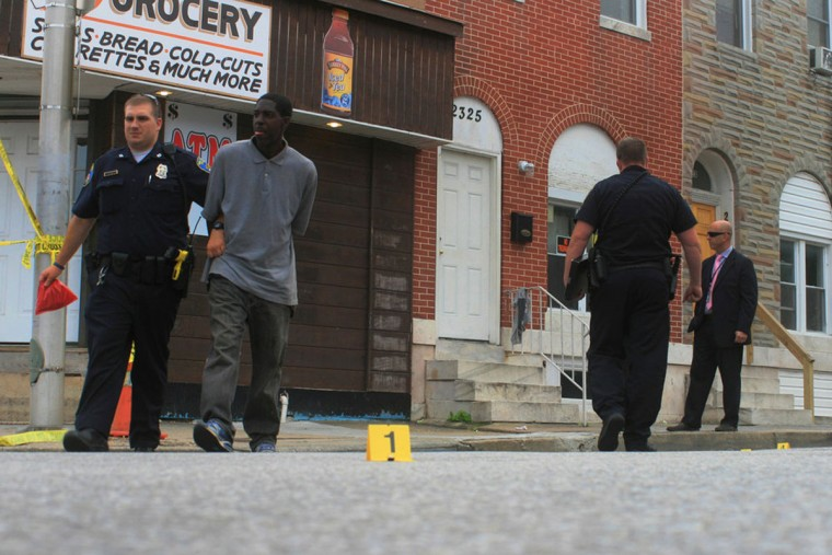 """A man sticks his tongue out at a detective as an officer escorts him from an East Baltimore shooting scene to a nearby police car."" (Photo and caption courtesy of Maggie Ybarra)"