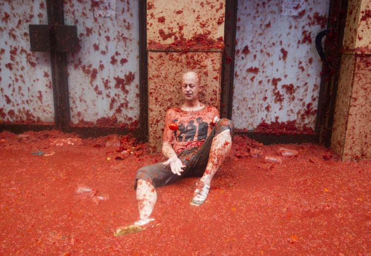 """A reveller covered in tomato pulp takes part in the annual """"Tomatina"""" festival in the eastern town of Bunol, on August 30, 2017. The iconic fiesta -- which celebrates its 72nd anniversary and is billed at """"the world's biggest food fight"""" -- has become a major draw for foreigners, in particular from Britain, Japan and the United States. (JAIME REINA/AFP/Getty Images)"""
