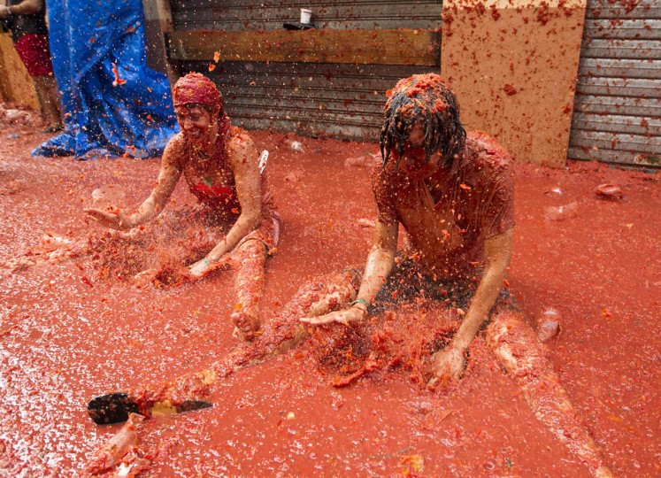 """Revellers covered in tomato pulp take part in the annual """"Tomatina"""" festival in the eastern town of Bunol, on August 30, 2017. The iconic fiesta -- which celebrates its 72nd anniversary and is billed at """"the world's biggest food fight"""" -- has become a major draw for foreigners, in particular from Britain, Japan and the United States. (JAIME REINA/AFP/Getty Images)"""