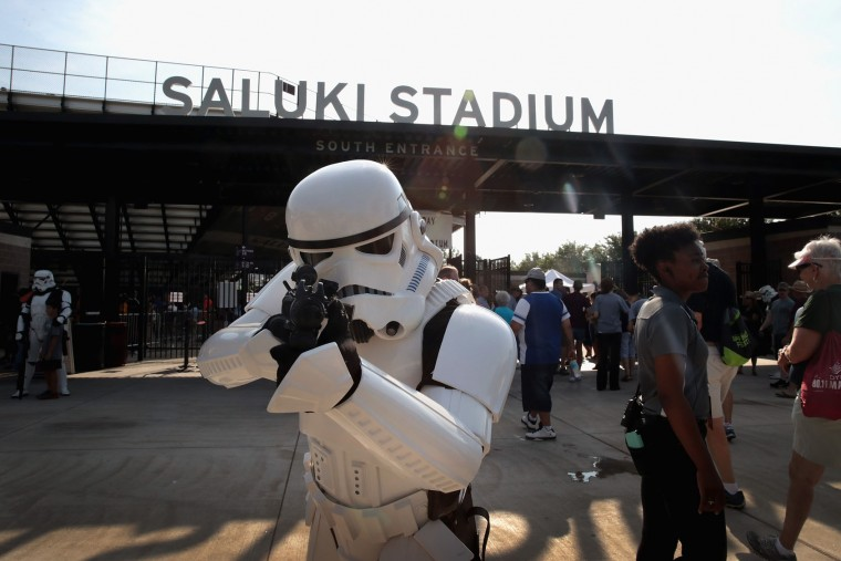 A person dressed as a Star Wars Stormtrooper poses as people arrive at Saluki Stadium on the campus of Southern Illinois University to watch the solar eclipse on August 21, 2017 in Carbondale, Illinois. With approximately 2 minutes 40 seconds of totality the area in Southern Illinois will experience the longest duration of totality during the eclipse. Millions of people are expected to watch as the eclipse cuts a path of totality 70 miles wide across the United States from Oregon to South Carolina on August 21. (Photo by Scott Olson/Getty Images)