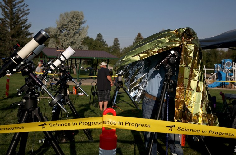 """People set up cameras and telescopes as they prepare to watch the total eclipse at South Mike Sedar Park on August 21, 2017 in Casper, Wyoming. Millions of people have flocked to areas of the U.S. that are in the """"path of totality"""" in order to experience a total solar eclipse. During the event, the moon will pass in between the sun and the Earth, appearing to block the sun. (Photo by Justin Sullivan/Getty Images)"""