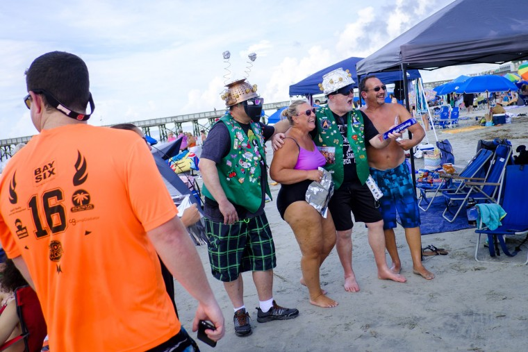 """Solar eclipse fans dressed in festive attire on the beach hoping to view the total solar eclipse if the weather clears on August 21, 2017 in Isle of Palms, South Carolina. It's been 99 years since a total solar eclipse crossed the country from the Pacific to the Atlantic. Millions of people have flocked to areas of the U.S. that are in the """"path of totality"""" in order to experience a total solar eclipse. During the event, the moon will pass in between the sun and the Earth, appearing to block the sun. Isle of Palms is one of last vantage points where totality will be visible. (Photo by Pete Marovich/Getty Images)"""