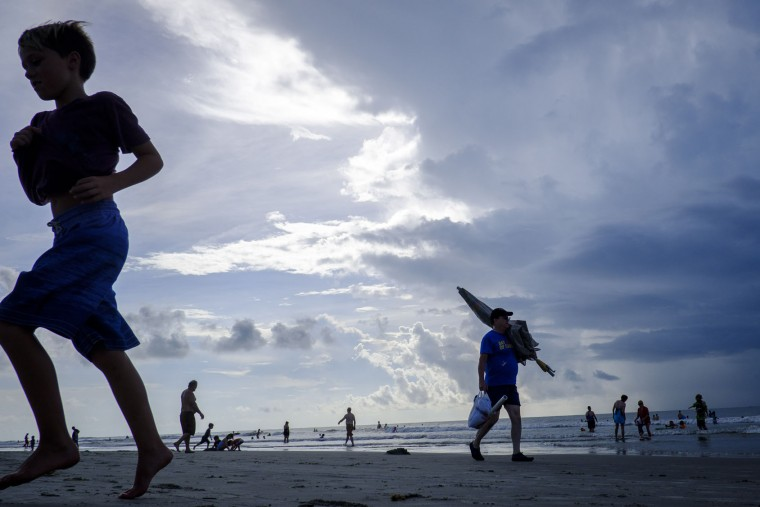 """Solar eclipse watchers on the beach hoping to view the total solar eclipse if the weather clears on August 21, 2017 in Isle of Palms, South Carolina. It's been 99 years since a total solar eclipse crossed the country from the Pacific to the Atlantic. Millions of people have flocked to areas of the U.S. that are in the """"path of totality"""" in order to experience a total solar eclipse. During the event, the moon will pass in between the sun and the Earth, appearing to block the sun. Isle of Palms is one of last vantage points where totality will be visible. (Photo by Pete Marovich/Getty Images)"""