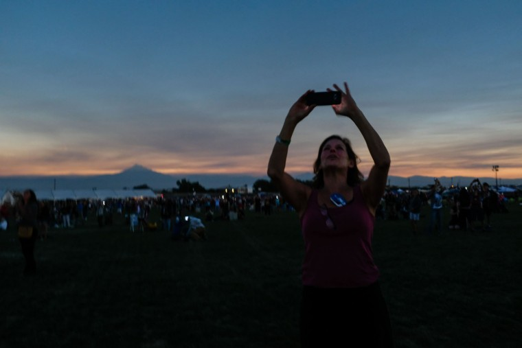 Barbara Hintzen of Edmonds, Washington records the sun during totality on August 21, 2017 in Madras, Oregon. Emotional sky-gazers stood transfixed across North America Monday as the Sun vanished behind the Moon in a rare total eclipse that swept the continent coast-to-coast for the first time in nearly a century. (Rob Kerr/AFP/Getty Images)