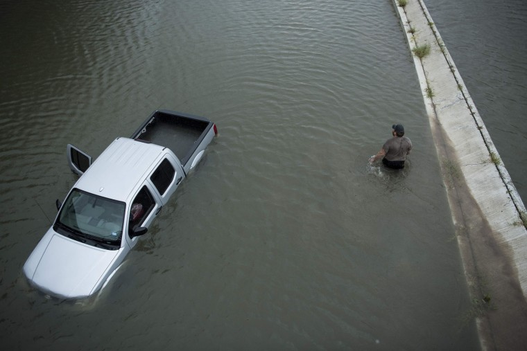 A truck driver walks past an abandoned truck while checking the depth of an underpass during the aftermath of Hurricane Harvey August 28, 2017 in Houston, Texas. Flood victims rest at a shelter in the George R. Brown Convention Center during the aftermath of Hurricane Harvey on August 28, 2017 in Houston, Texas. (Brendan Smialowski/AFP/Getty Images)