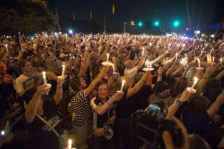 Fans hold candles during a vigil for Elvis Presley at Graceland, Presley's Memphis home, Tuesday, Aug. 15, 2017, in Memphis, Tenn. Fans from around the world are at Graceland for the 40th anniversary of his death. Presley died Aug. 16, 1977. (AP Photo/Brandon Dill)