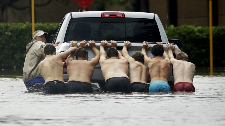People push a stalled pickup to through a flooded street in Houston, after Tropical Storm Harvey dumped heavy rains, Sunday, Aug. 27, 2017. The remnants of Hurricane Harvey sent devastating floods pouring into Houston on Sunday as rising water chased thousands of people to rooftops or higher ground. (AP Photo/Charlie Riedel)