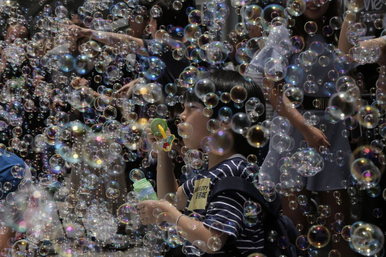 "A boy plays with bubbles during an art display titled ""Bubble Up"" created by Japanese artist Shinji Ohmaki in Hong Kong, Wednesday, Aug. 2, 2017. (AP Photo/Kin Cheung)"