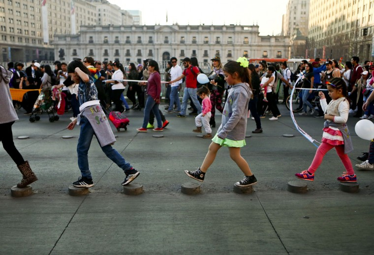 In this July 1, 2017 photo, transgender girls Selenna, center right, and Mathilda, far right, walk on street stumps with other children outside La Moneda government palace during a Gay Pride march in Santiago, Chile. The government is backing a bill that would give adults the right to change the official records of their gender, though the measure has stalled in Congress, facing challenges from the Roman Catholic church and other traditional forces. (AP Photo/Esteban Felix)