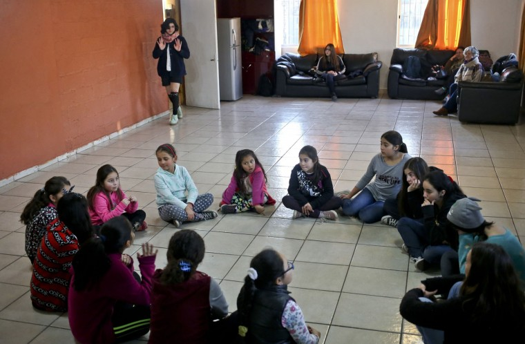 In this June 30, 2017 photo, transgender girls Angela, arriving, top, and Selenna, sitting in the circle at top left and wearing a blue sweatshirt, take a theater and dance class with girls at their community center Santiago, Chile. Angela, 13, who was born male, said she still struggles to come to terms with her identity a year after her transition, while Selenna, 8, said she always knew she was a girl. (AP Photo/Esteban Felix)