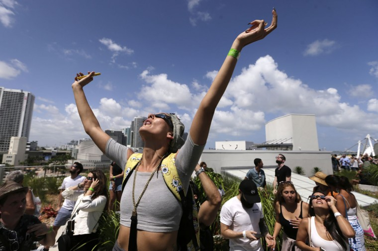 """A fashion designer who gave her name as """"Nonsense"""" watches a total solar eclipse from the roof of the Phillip and Patricia Frost Science Museum, Monday, Aug. 21, 2017, in Miami. (AP Photo/Lynne Sladky)"""