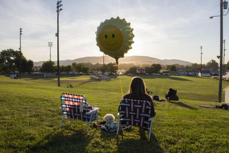 Katie Vega and her dog Toby wait for the solar eclipse in Weiser, Idaho, Monday, Aug. 21, 2017. Katie and her husband Vincent traveled from Sacramento. (AP Photo/Otto Kitsinger)