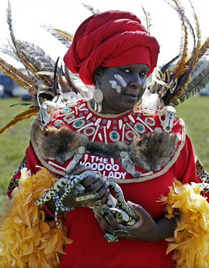 """The Voodoo Bone Lady of New Orleans poses with her snakes at the Orchard Dale historical farm near Hopkinsville, Ky., Monday, Aug. 21, 2017, The location, which is in the path of totality of the solar eclipse, is also at the point of greatest intensity. She said she chose to come to this location """"because I feel that in the recent weeks this country has gone toward hatred and division and I'm here to do a ritual toward peace and unity to hopefully reverse the trend of things."""" (AP Photo/Mark Humphrey)"""