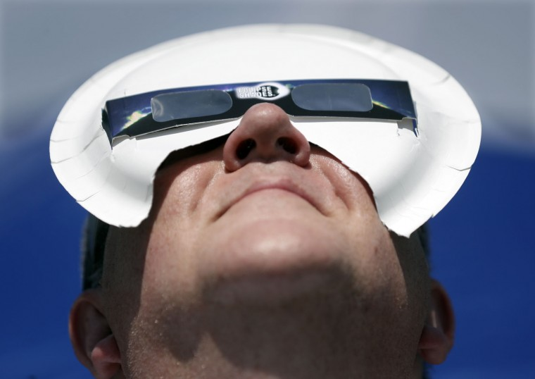 Tim Burt of Rochester, NY, uses a paper pate to hold his solar eclipse viewing glasses in place Monday, Aug. 21, 2017, on the Orchard Dale historical farm near Hopkinsville, Ky. The location, which is in the path of totality, is also at the point of greatest intensity. (AP Photo/Mark Humphrey)