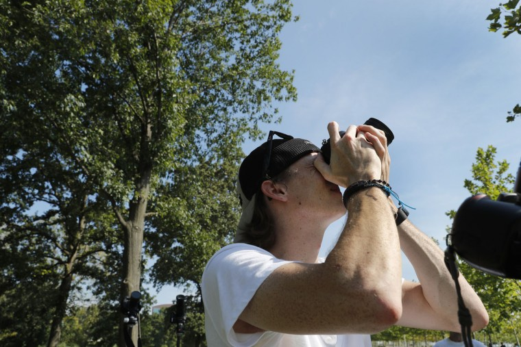 Ryan Oswald lines up his shot as he prepares for the solar eclipse at the Gateway Arch Monday, Aug. 21, 2017, in St. Louis. The Gateway Arch sits a few miles outside of the path of totality. (AP Photo/Jeff Roberson)