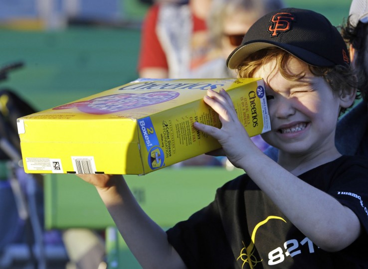 Griffin O'Roak watches the rising sun with his homemade eclipse viewer at a gathering of eclipse viewers in Salem, Ore., Monday, Aug. 21, 2017. (AP Photo/Don Ryan)