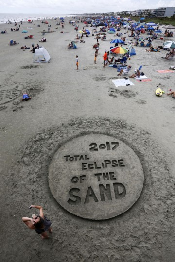 """Beach goers look up during a solar eclipse Monday, Aug. 21, 2017, on the beach at Isle of Palms, S.C. The city of Isle of Palms hosted a beach party """"Get Eclipsed on IOP"""". (AP Photo/Mic Smith)"""