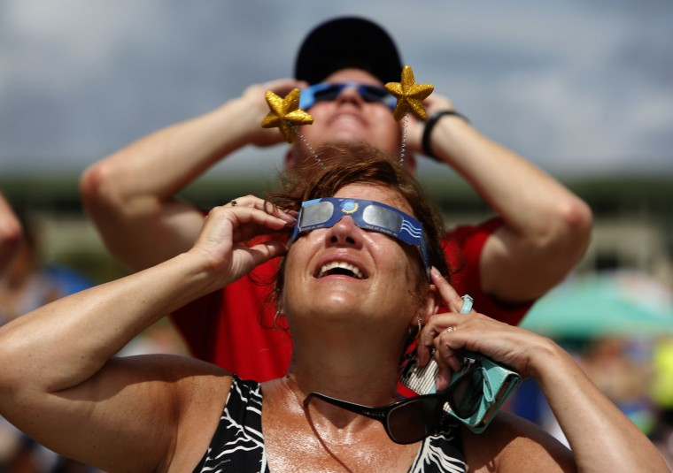 """Beth Christie, in front, from Pembroke, N.H., and Andy Sinwald, who works for the Isle of Palms, S.C. Recreation Department, look up during the solar eclipse Monday, Aug. 21, 2017, on the beach at Isle of Palms, S.C. The city of Isle of Palms hosted a beach party """"Get Eclipsed on IOP"""". (AP Photo/Mic Smith)"""