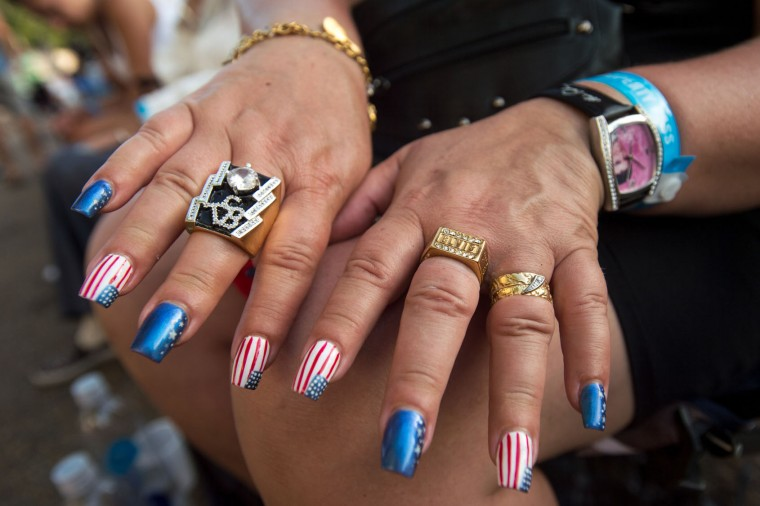 Pernilla Gulaker, from Sweden, shows off her Elvis-themed jewelry and American flag-inspired fingernails during a candlelight vigil for Elvis Presley at Graceland, Presley's Memphis home, on Tuesday, Aug. 15, 2017, in Memphis, Tenn. Fans from around the world are at Graceland for the 40th anniversary of the rock n' roll icon's death. Presley died Aug. 16, 1977. (AP Photo/Brandon Dill)