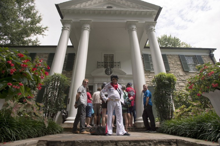 Glasgow, Scotland, resident Bryan Glencross strikes a pose in his Elvis-inspired outfit while waiting to begin a tour of Graceland, Elvis Presley's Memphis home, on Tuesday, Aug. 15, 2017, in Memphis, Tenn. Fans from around the world are at Graceland for the 40th anniversary of the rock n' roll icon's death. (AP Photo/Brandon Dill)