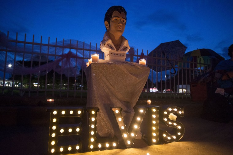 A street memorial is lit during a candlelight vigil for Elvis Presley in front of Graceland, Presley's Memphis home, on Tuesday, Aug. 15, 2017, in Memphis, Tenn. Fans from around the world are at Graceland for the 40th anniversary of his death. Presley died Aug. 16, 1977. (AP Photo/Brandon Dill)