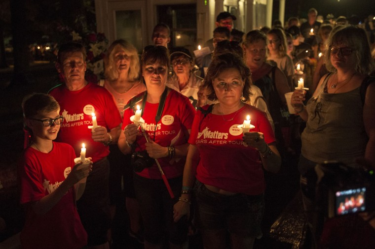 Visitors participate in a candlelight vigil for Elvis Presley at Graceland, Presley's Memphis home, on Tuesday, Aug. 15, 2017, in Memphis, Tenn. Fans from around the world are at Graceland for the 40th anniversary of his death. Presley died Aug. 16, 1977. (AP Photo/Brandon Dill)