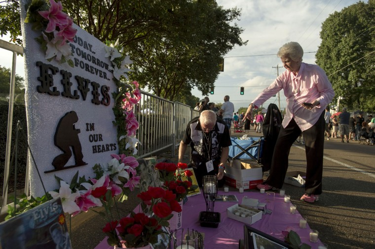 Roger Engelby, left, and Jerry Engelby set up their street memorial before a candlelight vigil for Elvis Presley at Graceland, Presley's Memphis home, on Tuesday, Aug. 15, 2017, in Memphis, Tenn. The Jefferson City, Missouri residents have been to every vigil at Graceland since 1993. Fans from around the world are at Graceland for the 40th anniversary of the rock n' roll icon's death. Presley died Aug. 16, 1977. (AP Photo/Brandon Dill)