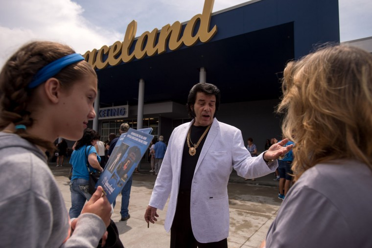 Elvis tribute artist Tony Grova, center, talks with Madison Pugsley, 12, left, and her grandmother Marie Geering at Elvis Presley's Memphis near Graceland, Presley's Memphis home, on Tuesday, Aug. 15, 2017, in Memphis, Tenn. Fans from around the world are at Graceland for the 40th anniversary of his death. Presley died Aug. 16, 1977. (AP Photo/Brandon Dill)