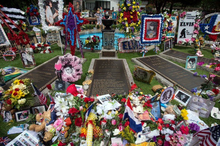 Flowers, signs, and other tributes left by fans fill the meditation garden where Elvis Presley is buried alongside his parents and grandmother at Graceland, Presley's Memphis home, on Tuesday, Aug. 15, 2017, in Memphis, Tenn. Fans from around the world are at Graceland for the 40th anniversary of his death. Presley died Aug. 16, 1977. (AP Photo/Brandon Dill)