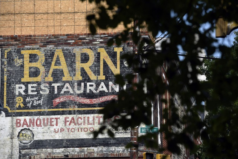 "An advertisement for The Barn Restaurant painted on a building on Hull St. and Fort Ave. The Glen Burnie restaurant burned in a ""suspicious"" fire in 1974. (Kim Hairston/Baltimore Sun)"