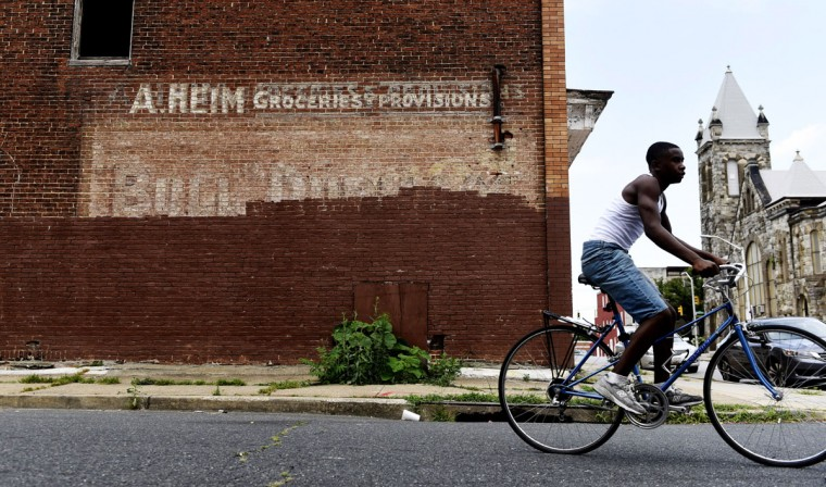 A. Heim Groceries and Provisions remains above a faded and partially painted over Bull Durham sign on the corner of Riggs and McKean in West Baltimore. (Kim Hairston/Baltimore Sun.)