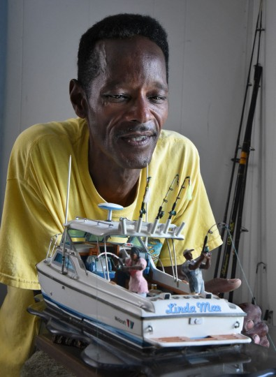 "Norman Gross, 58, looks at his model of the ""Linda Mae,"" a fishing boat he owned and used for fishing with his wife. It was a ""gorgeous"" boat that ""stayed on course, just like a Cadillac,"" Gross recalls. He builds model boats that pay homage to an earlier generation of African-American watermen on the Chesapeake. (Amy Davis / The Baltimore Sun)"