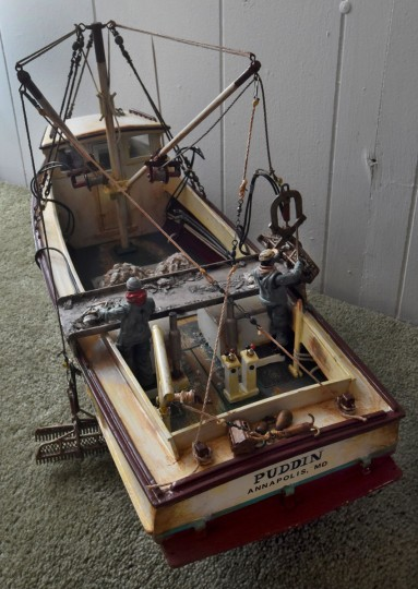 """Norman Gross created this replica of """"Puddin,"""" a workboat operated by his uncle, Rodney Gross, for oystering in the winter and clamming in the summer. Rodney's son, J.R. Gross, sorts oysters on the culling board at left. The workboat was a converted cabin cruiser. (Amy Davis / The Baltimore Sun)"""