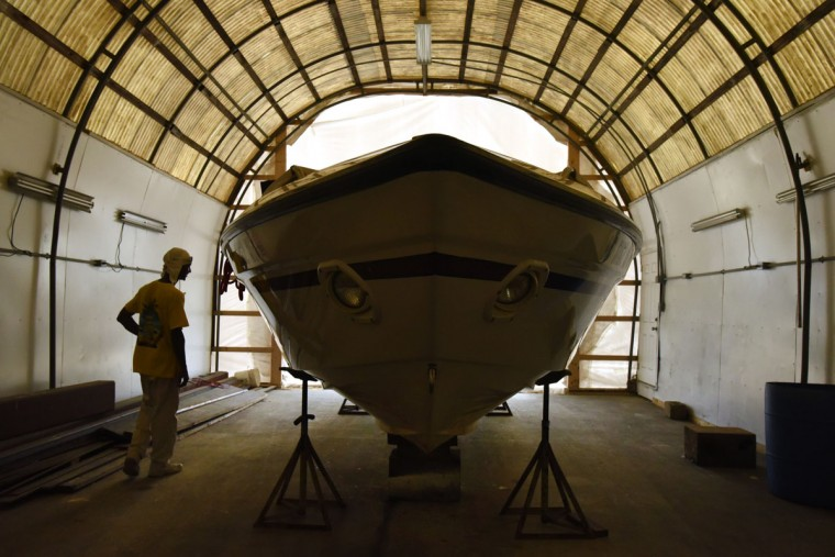 Norman Gross surveys a boat's gleaming surface after sanding, painting and applying two clear coats to its hull, at the South River Marina where he works as a gelcoat and fiberglass technician. Gross, 58, builds small model boats that pay homage to an earlier generation of African-American watermen on the Chesapeake. (Amy Davis / The Baltimore Sun)