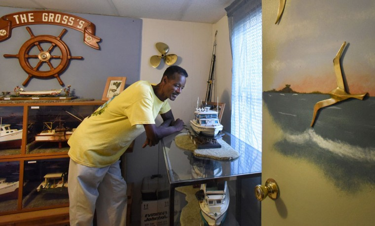 "Norman Gross looks over the ""Linda Mae,"" which he took out of one of the display cabinets he built to house his collection of nine model workboats that show African-American watermen on the Chesapeake. (Amy Davis / The Baltimore Sun)"