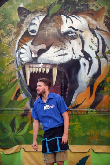 Justin Butler who works at the Big Al's Safari game, is pictured near the tiger mural. (Lloyd Fox/Baltimore Sun)