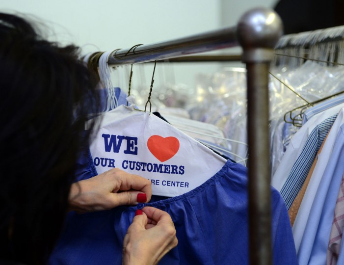 Shirley Tsao, whose family owns TC Wing Laundry in Roland Park, buttons a blouse she has just ironed.