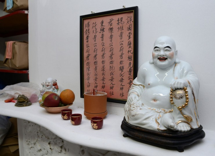 A buddha on a shelf at T.C. Wing Laundry was brought from China by the laundry's founder, T.C. Wing, who is the grandfather of the current owners. The framed poster has writings that are a tribute to the family's ancestors.